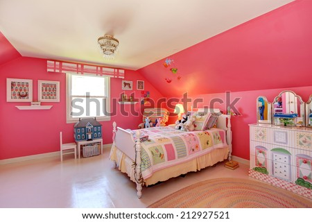 Beautiful girls room in bright pink color with carved wood bed and toys - stock photo