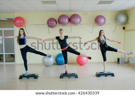 Beautiful girls spend aerobics morning exercises in a fitness room
