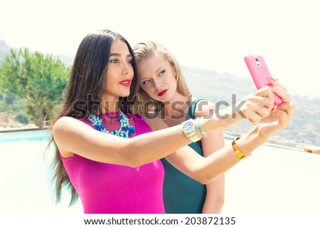 Beautiful girls taking a selfie with their cell phone - stock photo