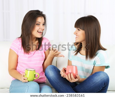 Beautiful girls twins drinking tea at home