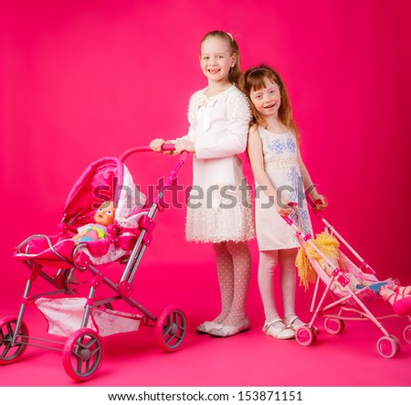 beautiful girls with dolls and toy strollers - stock photo