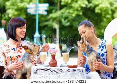 beautiful girls with pets sitting in street cafe - stock photo