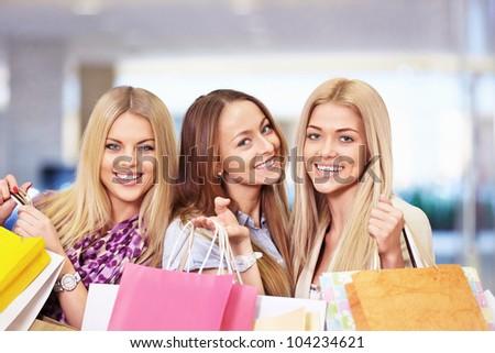 Beautiful girls with shopping bags in shop - stock photo