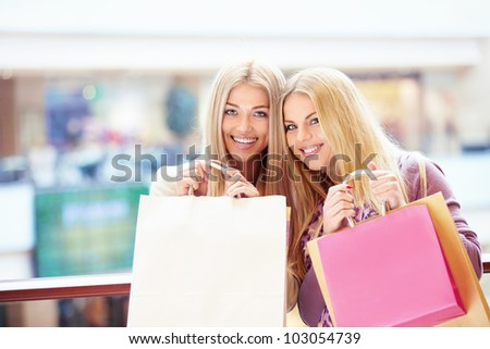 Beautiful girls with shopping bags in store - stock photo