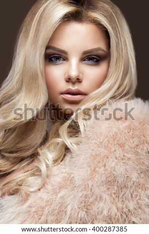 Beautiful glamor blondie woman in fur coat , evening makeup and curls. The beauty of the face.