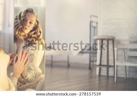 Beautiful glamor young woman in a white dress looking to the mirror in bright room  - stock photo