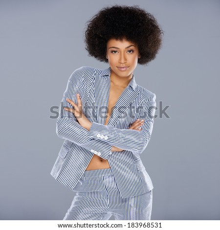 Beautiful glamorous Afro-American woman in a stylish tailored striped slack suit standing looking at the camera with folded arms and a confident amused expression - stock photo