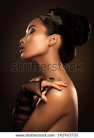 Beautiful glamorous Asian woman posing in front of a brown background. - stock photo