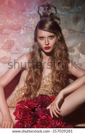 Beautiful glamorous brunette girl with curly long hair. Studio shot. Bright makeup with red lipstick. Beauty. Sexy girl in gold underwear. With red roses. Queen in crown. - stock photo