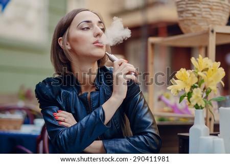 beautiful glamorous brunette smoke electronic cigarette - stock photo