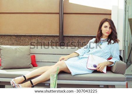 Beautiful glamorous girl in a dress with a clutch. Rest after shopping. Luxury girl in a checkered dress. Girl with sunglasses. Fashion & Style. Stylish Girl. - stock photo
