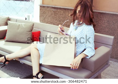Beautiful glamorous girl in a dress with a paper sack. Rest after shopping. Luxury girl in a checkered dress. Space for text. Girl with sunglasses. Fashion & Style. Stylish Girl. - stock photo