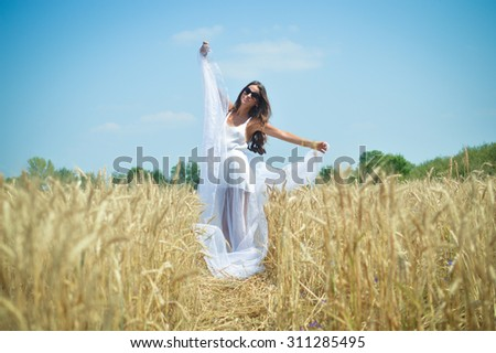 Beautiful glamour girl dancing in the wheat field and breathing deep fresh air. Long haired woman in sunglasses posing for photographer with white cloth.