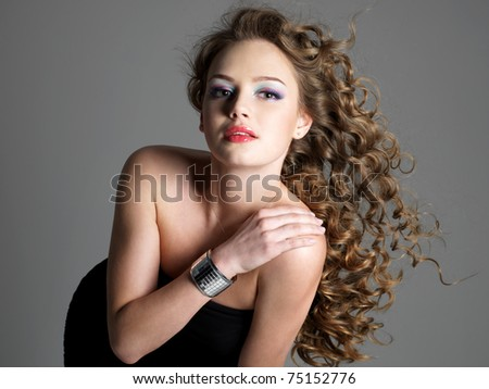 Beautiful glamour portrait of young stylish woman with long hair posing at studio
