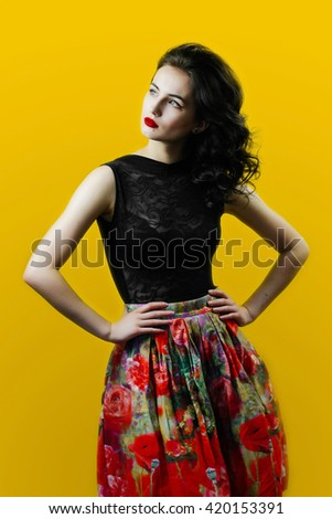 Beautiful glamour retro sexy woman in pinup style in flower skirt and unusual pose. Emotional colorful warm excited spring style photo of brunette on orange background. - stock photo