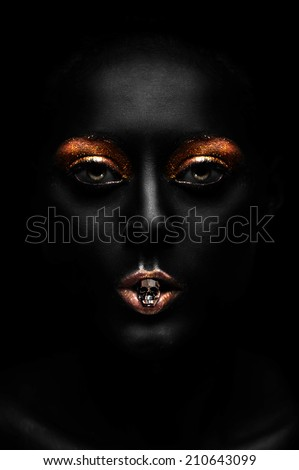 Beautiful Glamour woman with face painted in black on black background - stock photo