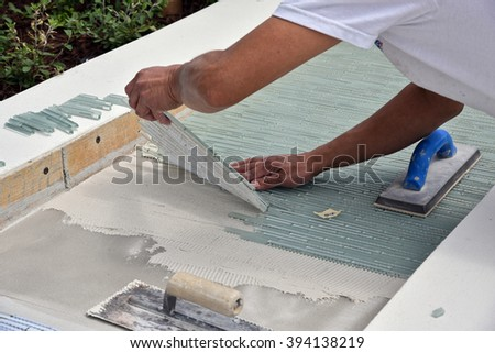 Beautiful glass ceramic tiles being installed by a skilled contractor. - stock photo