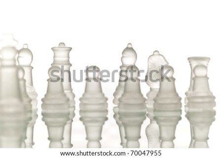 Beautiful glass chess on a white background. Photo taken in the studio on a glass countertop