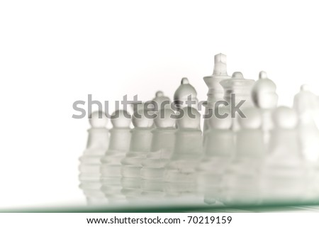 Beautiful glass chess on a white background. Photo taken in the studio on a glass countertop.