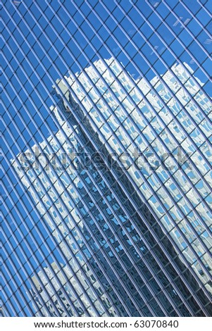 Beautiful glass office building with blue reflections of surrounding buildings - stock photo