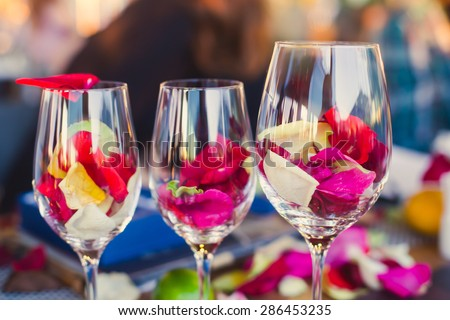 Beautiful glass with rose leafs, rose-petal, rose petals on a romantic date with wine, candles in candlelight and with celebrating couple on the background, interior for a romantic date diner  - stock photo