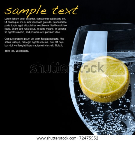 Beautiful glass with sparkling water or other transparent drink and a slice of lemon on black background