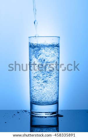 Beautiful glass with water on a blue background with bubbles