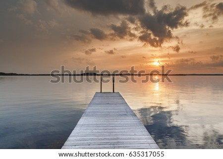 Beautiful glowing orange sunset over a rustic timber plank jetty reflected in the mirror calm waters of the sea below, a background of natural beauty and serenity. Northern sea, Sweden, Scandinavia.