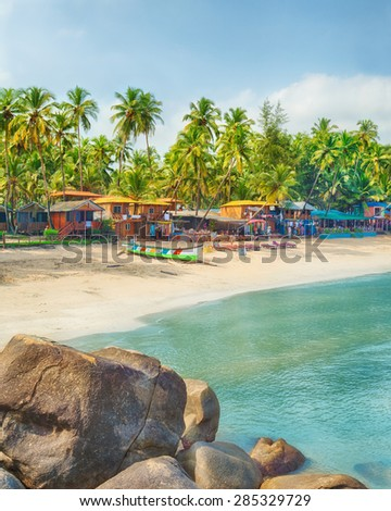 Beautiful Goa province beach in India with fishing boats and stones in the sea  - stock photo