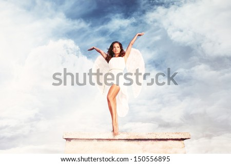 beautiful goddess like young brunette woman  with angel wings and white dress against sky with clouds , full body shot, outdoor