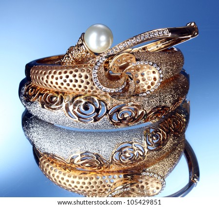 Beautiful gold bracelets on blue background - stock photo