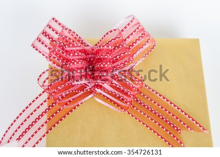 Beautiful gold present box with red bow on white paper backgound - stock photo
