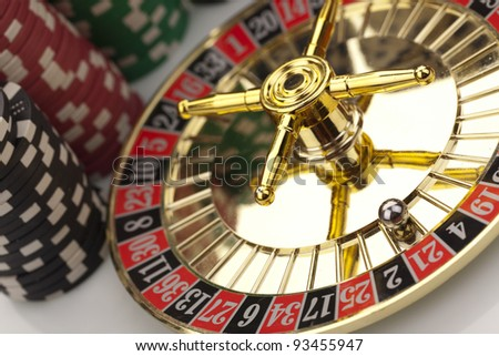 Beautiful gold roulette with casino chips on a white background.