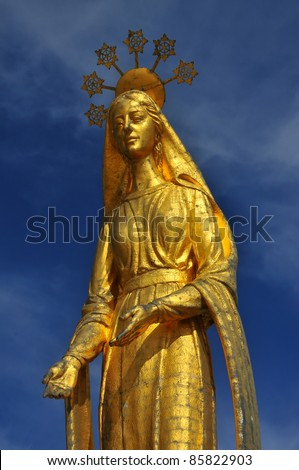 Beautiful Gold statue of the virgin Mary standing on the top of an ancient pass between Italy and Switzerland. the halo containing snowflakes, reflecting the altitude