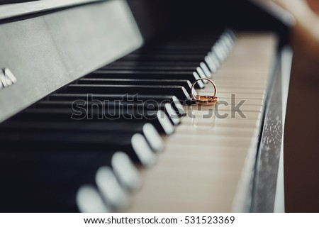 beautiful gold wedding rings lying on the keys of a piano