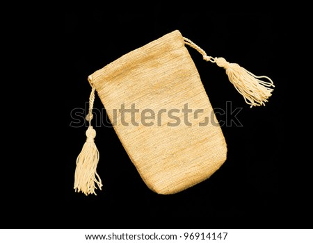 Beautiful Gold / Yellow Silk bag / pouch to hold jewelry and delicate items isolated on black background - stock photo