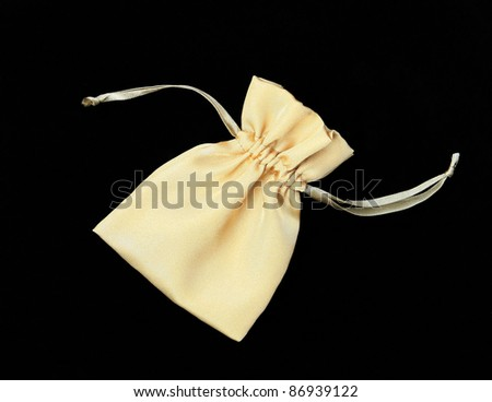 Beautiful Gold / Yellow Silk Pouch to hold Jewelry and Delicate items isolated on Black Velvet Background - stock photo