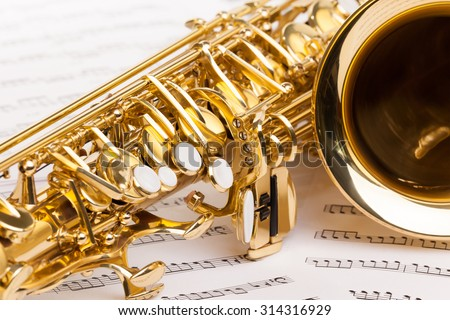 Beautiful golden alto saxophone fragment on the musical notes  - stock photo