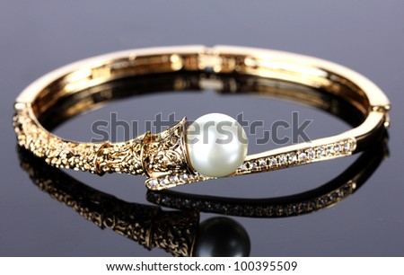 Beautiful golden bracelet with pearl on grey background - stock photo