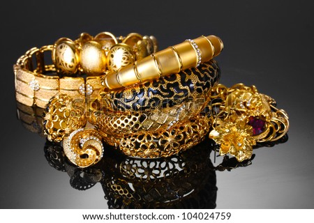 Beautiful golden bracelets, rings and jewelry on grey background