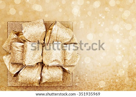 Beautiful golden gift against a bokeh background with copy space. - stock photo