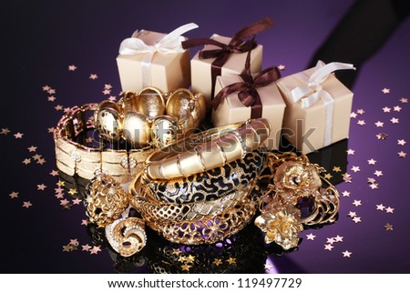 Beautiful golden jewelry and gifts on grey background - stock photo