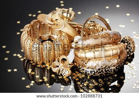 Beautiful golden jewelry on grey background - stock photo