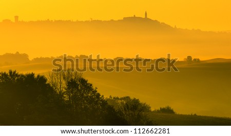 Beautiful golden light at sunrise in Tuscany near the village of San Quirico d'Orcia - stock photo