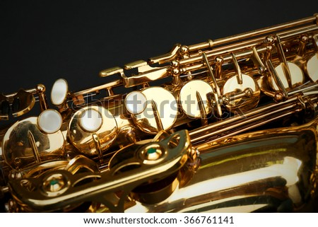 Beautiful golden saxophone on black background, close up