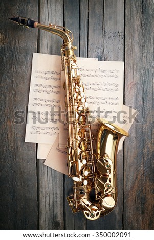 Beautiful golden saxophone with musical notes on wooden background, close up - stock photo