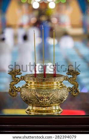 Beautiful golden spiritual vase or stupa with head of dragon engraved on its body and smoking aromatic candles in it.