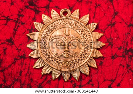 Beautiful golden sun face made of brass used as a decoration or jewellery - stock photo