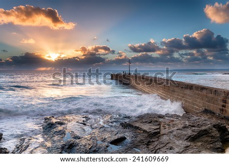 Beautiful golden sun rays as it sets over the stone pier at Porthleven on the Cornwall coast - stock photo
