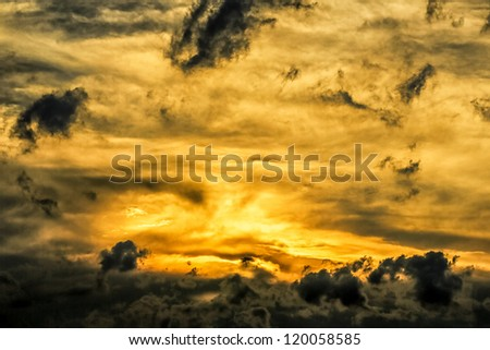 Beautiful golden sun setting behind the dark stormy clouds over the skies of Johannesburg city - stock photo